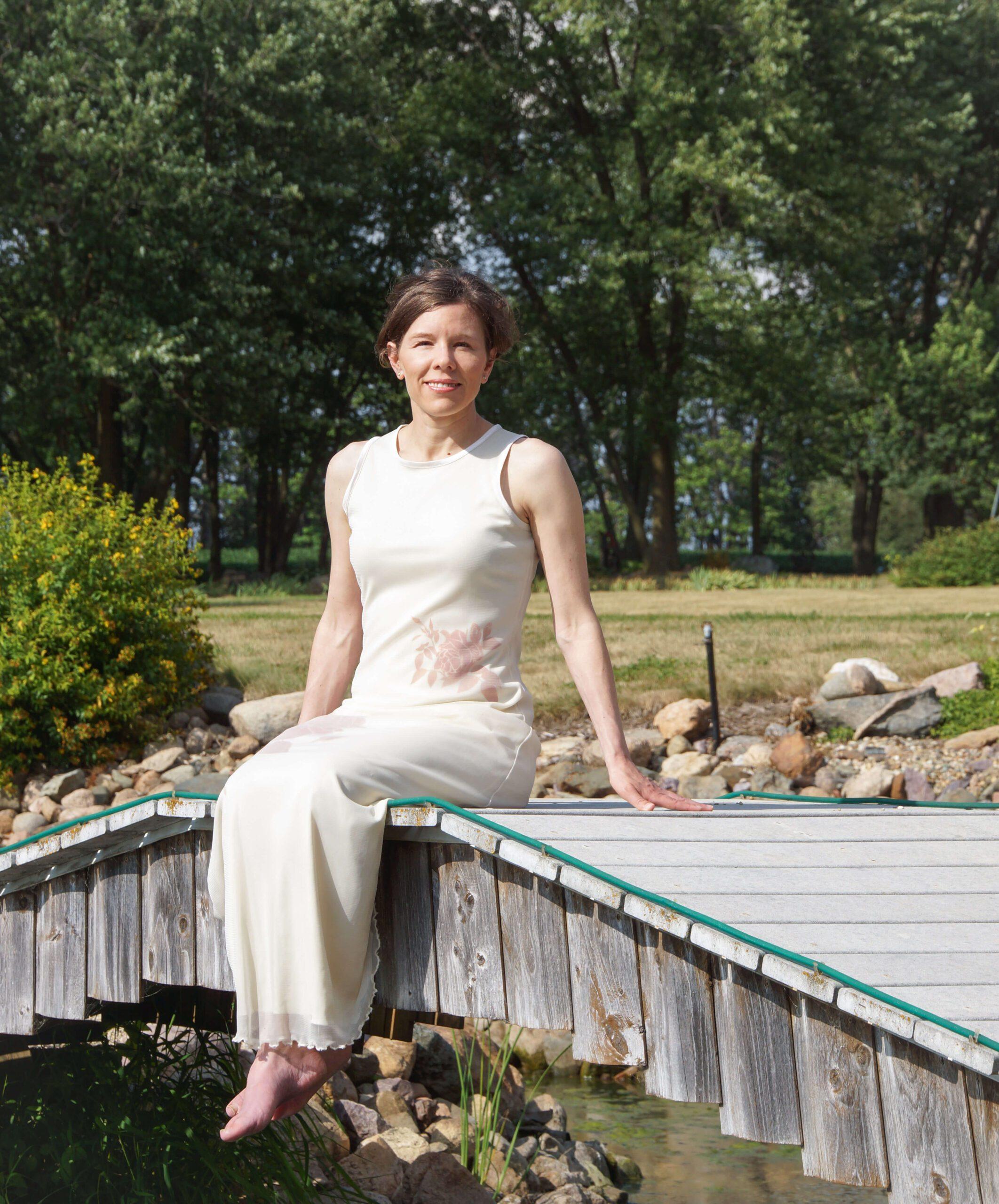 Farrah Fritz sitting on a wooden bridge
