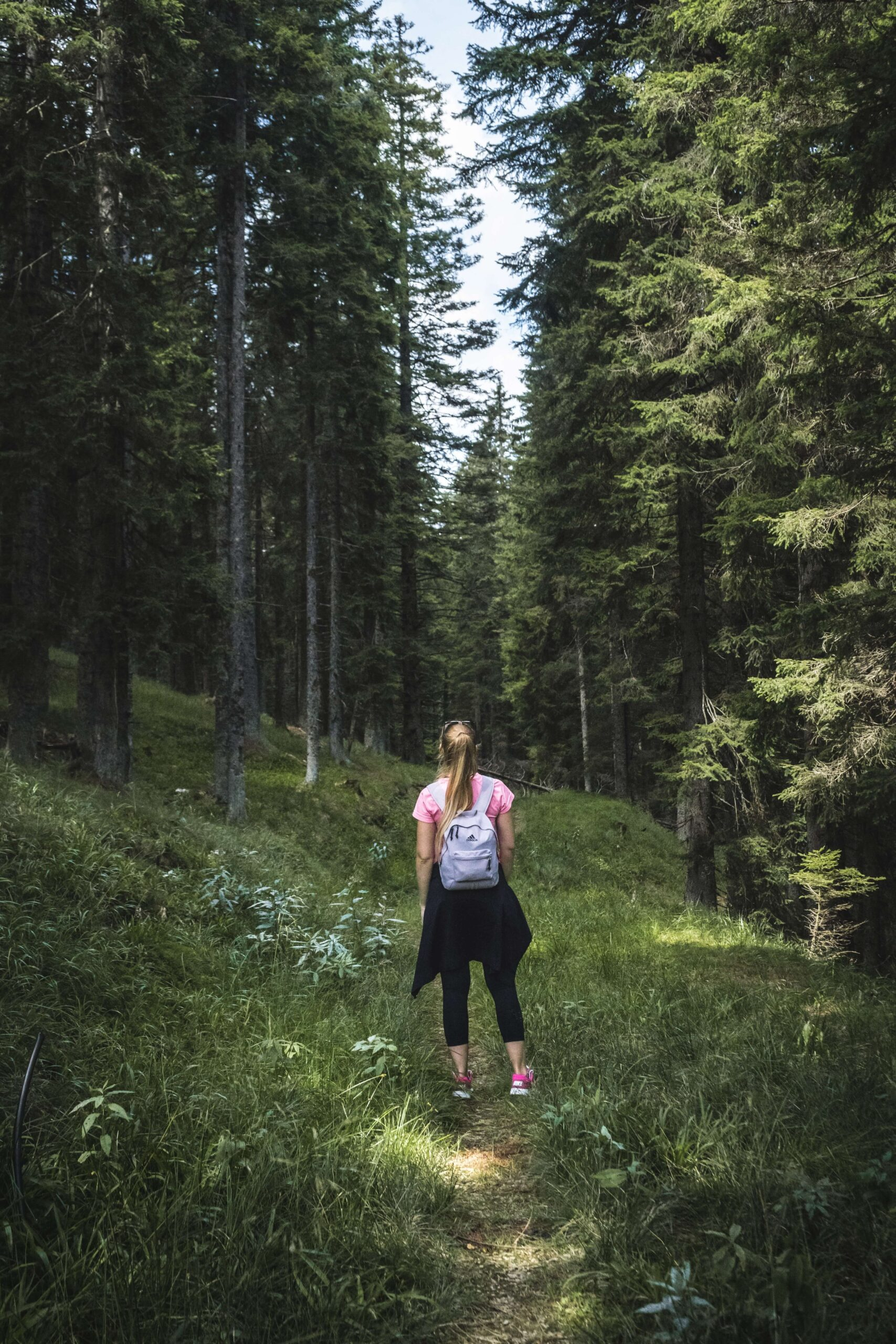 Woman walking through forest with backpack